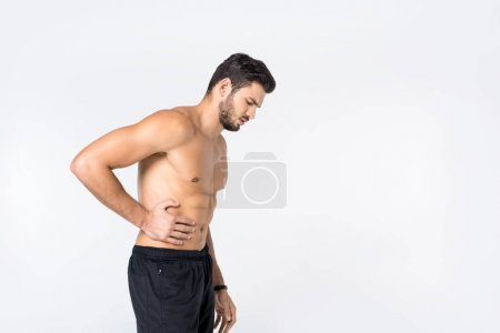 side view of shirtless young man with stomachache isolated on white