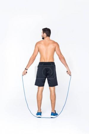 back view of young shirtless sportsman jumping over rope isolated on white