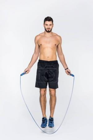 Photo for Young shirtless sportsman jumping over rope isolated on white - Royalty Free Image