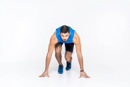 handsome young sprinter in start position isolated on white