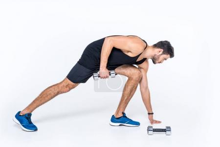 handsome young man working out with dumbbells on white