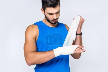 young man covering wrist with bandage isolated on white