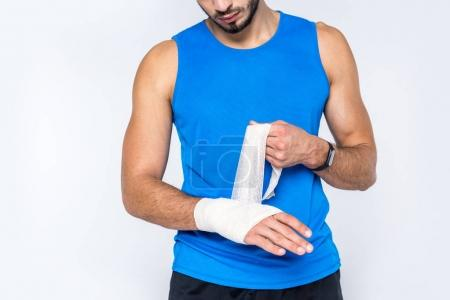 cropped shot of young man covering wrist with bandage isolated on white