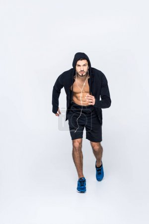 sportive young jogger with earphones running at camera on white