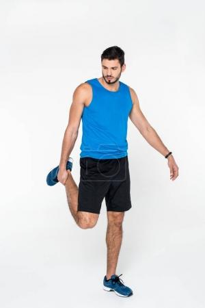 young jogger stretching leg before run isolated on white