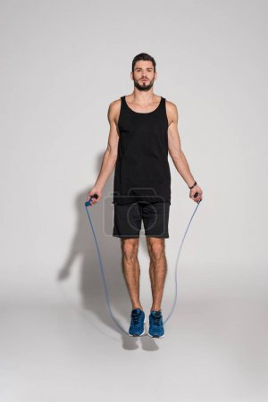 sportive young man jumping with rope on white