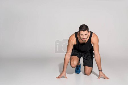 Photo for Handsome young runner in start position on white - Royalty Free Image