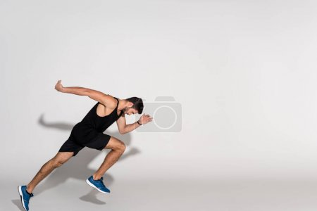 side view of young man running on white
