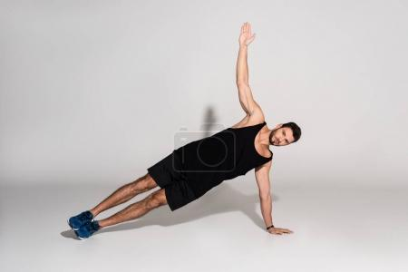 Photo for Sportive young man doing side plank - Royalty Free Image