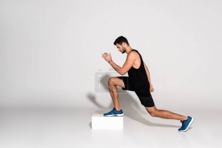 Photo for Side view of athletic man doing step aerobics on block - Royalty Free Image