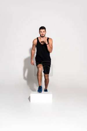 handsome young man doing step aerobics on block