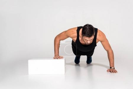handsome young man doing push ups with one hand on block