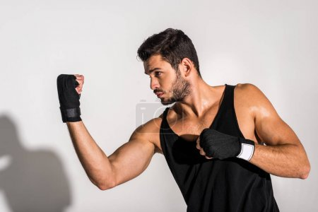 Photo for Side view of young fighter making hit - Royalty Free Image