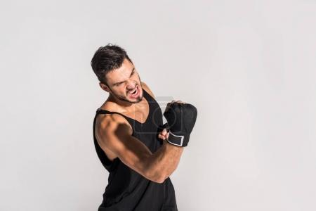 Photo for Agressive screaming fighter making hit isolated on grey - Royalty Free Image