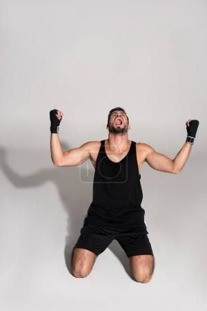 shouting fighter standing on knees on white surface