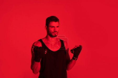 handsome young fighter with hands covered with bandages under red light
