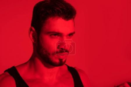 close-up portrait of handsome young man under red light