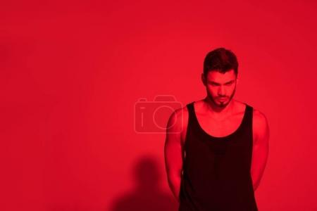 angry young man under contrast red light
