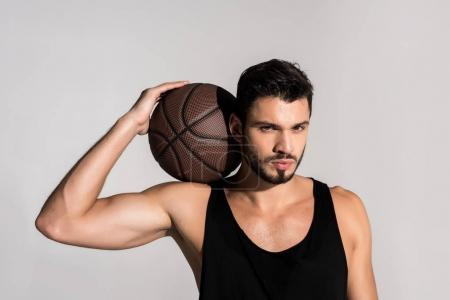 handsome young basketball player with ball isolated on grey