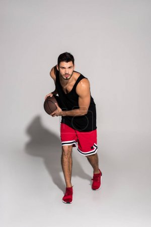 handsome young basketball player running with ball