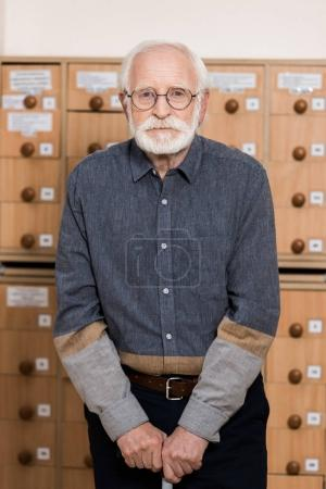 senior male archivist leaning on walking stick and looking at camera