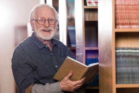 smiling grey hair librarian holding book and looking at camera