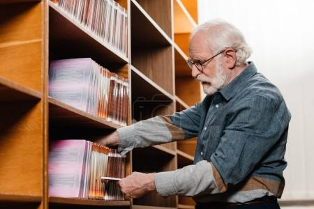 side view of grey hair librarian searching for book