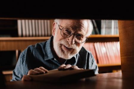 smiling grey hair librarian looking at camera through shelf