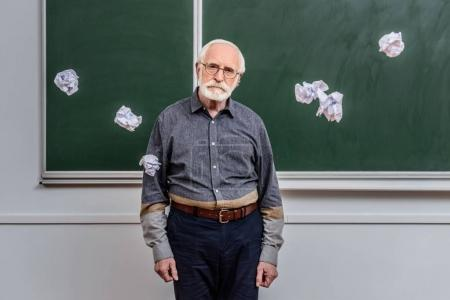 senior lecturer standing between falling crumpled pieces of paper