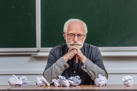 senior lecturer looking at crumpled pieces of paper on table