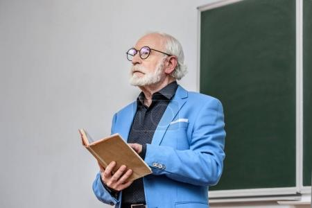 senior lecturer holding book and looking away
