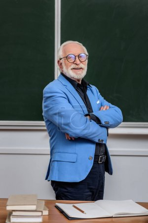 smiling grey hair professor standing with crossed arms