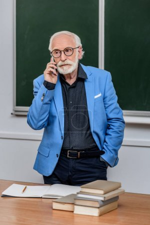 grey hair professor talking by smartphone and looking away