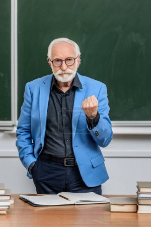 grey hair professor showing fist to students