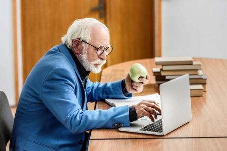 grey hair professor holding apple and using laptop