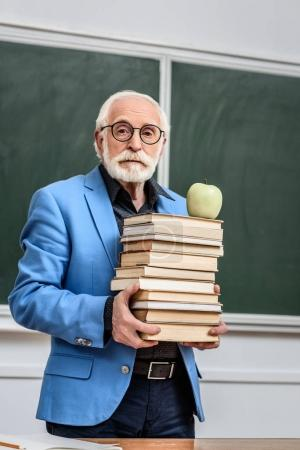grey hair professor holding stack of books with apple on top