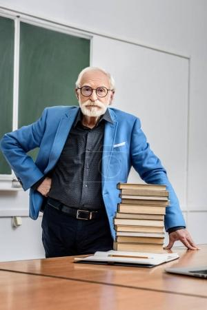 grey hair professor standing near stack of books
