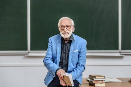 grey hair professor sitting on table in lecture room and holding book