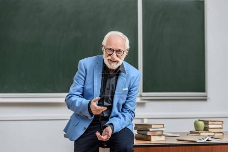 smiling grey hair professor sitting on table in lecture room