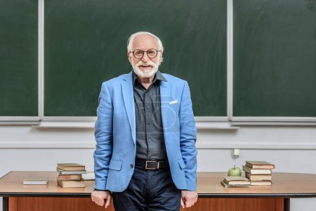 smiling grey hair professor standing in lecture room and looking at camera