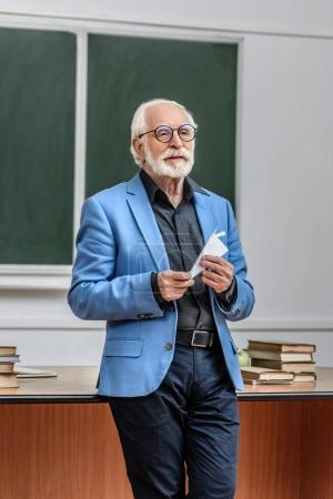 grey hair professor holding paper plane in lecture hall