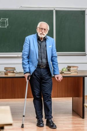 grey hair professor leaning on table and walking stick
