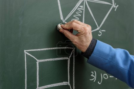 cropped image of professor drawing with piece of chalk at blackboard
