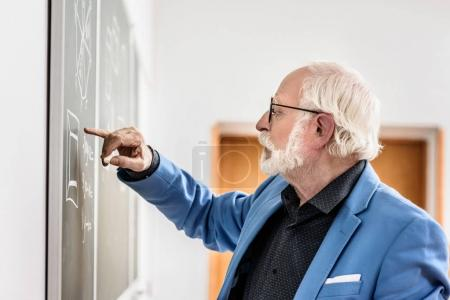 side view of grey hair professor correcting something at blackboard