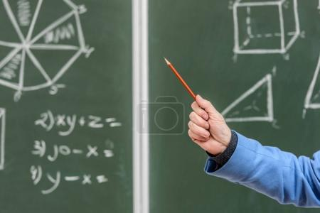 cropped image of senior professor pointing on something with pencil on blackboard