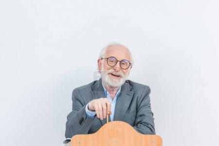 happy senior lecturer standing at wooden tribune isolated on white