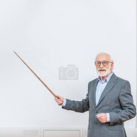 smiling senior lecturer pointing on something at white screen with wooden pointer