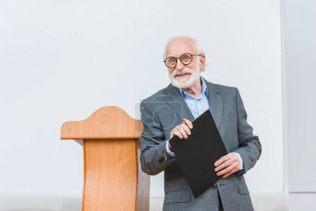 Photo pour Maître de conférences souriant tenant presse-papiers et en regardant la caméra - image libre de droit