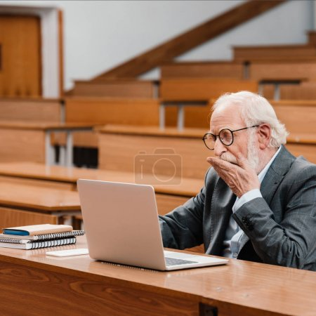grey hair professor yawning in empty lecture room