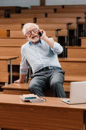 smiling grey hair professor sitting on desk in empty lecture room and talking by smartphone